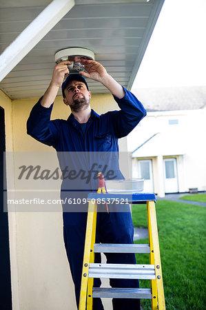 Handyman testing a light bulb