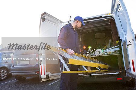 Handyman loading a ladder