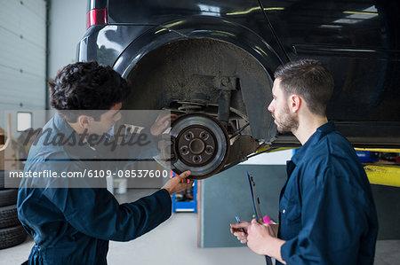 Mechanics examining car brake