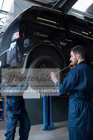 Mechanics changing car wheel