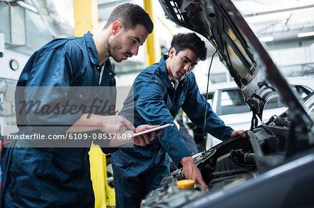 Mechanics examining car engine using digital tablet
