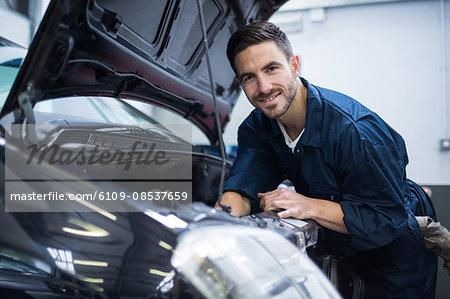 Mechanic smiling at camera while examining car engine