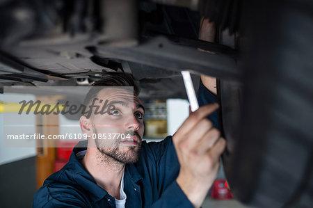 Mechanic examining car tyre