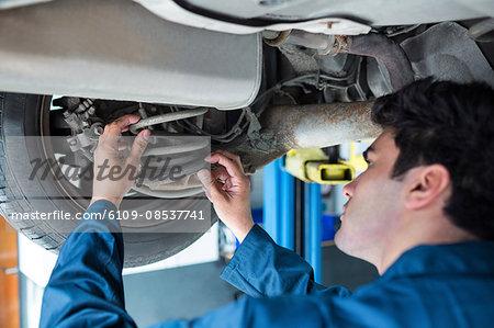 Mechanic repairing suspension of a car