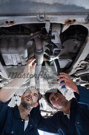 Mechanics examining silencer of a car using flashlight