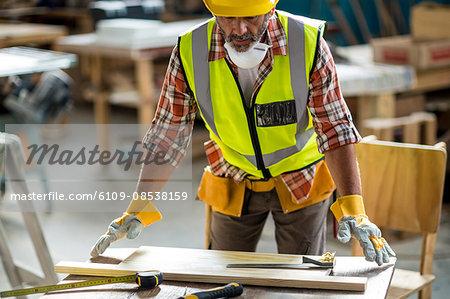 Carpenter measuring wooden plank