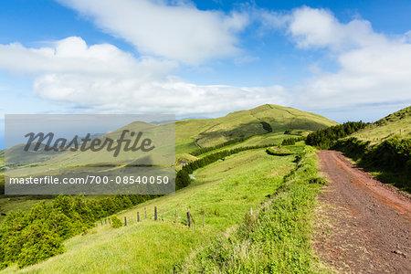 Rural dirt road through green landscape with volcanic craters, beneath the volcanic formation of Pico da Esperanca (1052 m) mountain, Norte Grande, Sao Jorge Island, Azores, Portugal