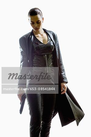 Female spy holding gun while walking against white background