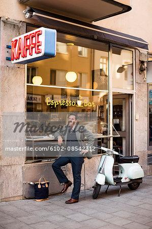 Mature man sitting at sidewalk cafe
