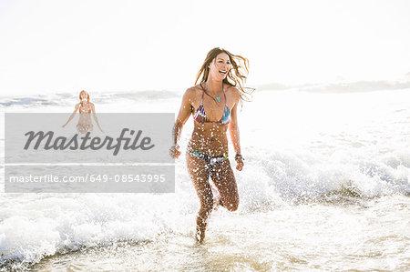 Two women wearing bikini's running in sea, Cape Town, South Africa