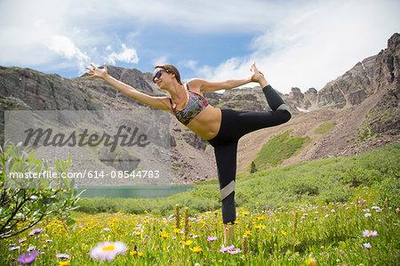 Woman practising yoga on meadow, Cathedral Lake, Aspen, Colorado