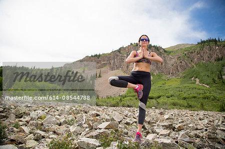 Woman practising yoga on rocks, Aspen, Colorado