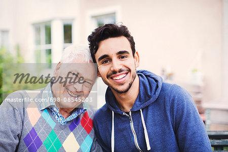 Portrait of happy senior man with caretaker sitting outdoors