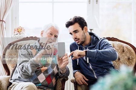 Caretaker assisting elderly man in using mobile phone at nursing home