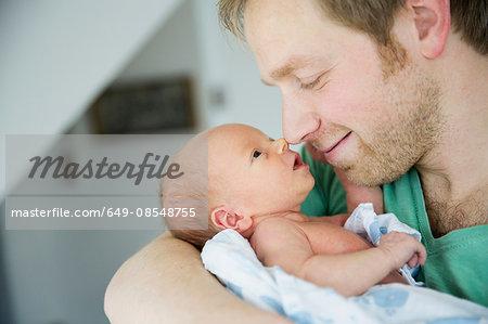 Father cradling baby boy, nose to nose smiling