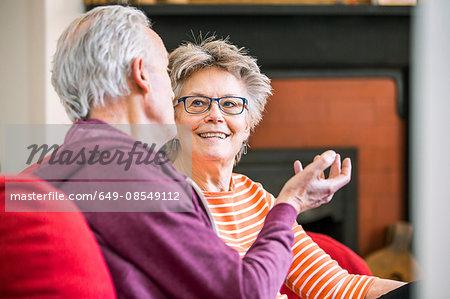 Senior couple on living room sofa chatting