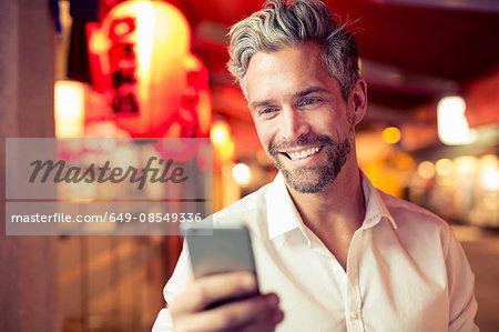 Man looking at smartphone smiling