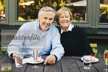 Portrait of happy senior couple having dessert at outdoor restaurant