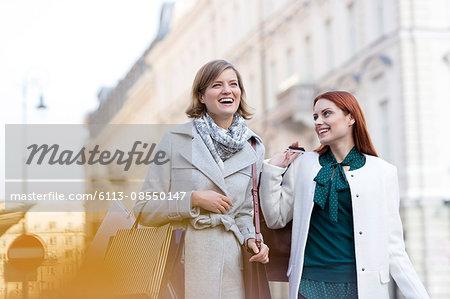 Smiling women carrying shopping bags in city