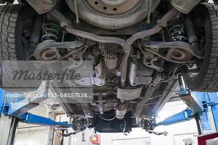Car on hydraulic stand in garage
