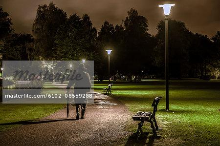 Man walking through park at night, Ronneby, Blekinge, Sweden