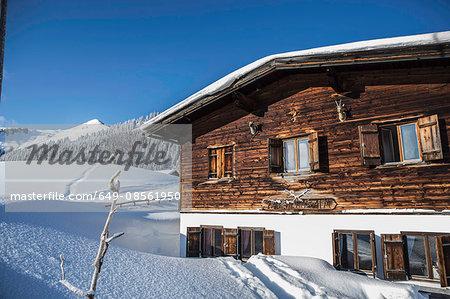Log cabin on snowy mountainside