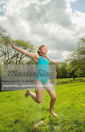 Young girl jumping over garden sprinkler in field