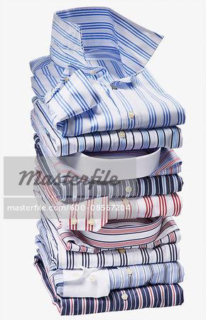 Stack of multi coloured, striped shirts on white background, studio shot