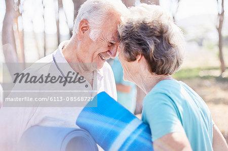 Affectionate senior couple holding yoga mats in park