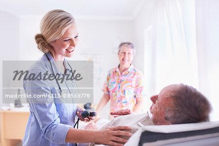 Doctor checking senior man's blood pressure in examination room