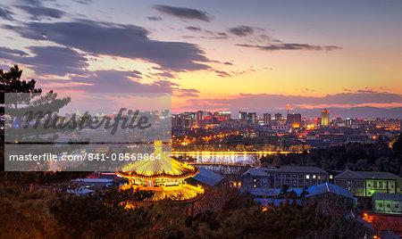 Illuminated pagoda and view towards the western part of Beijing city at nightfall, Beijing, China, Asia