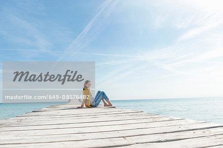 Mid adult woman sitting on pier, wearing headphones