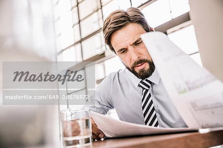 Bearded businessman looking down at paperwork