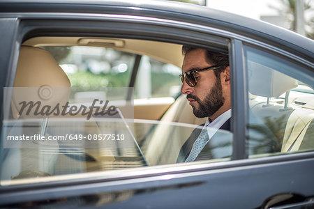 Young businessman using digital tablet in car backseat, Dubai, United Arab Emirates