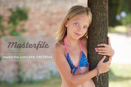 Portrait of girl wearing bikini top leaning against tree, Buonconvento, Tuscany, Italy