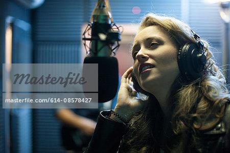 Female musician in recording studio, singing into microphone