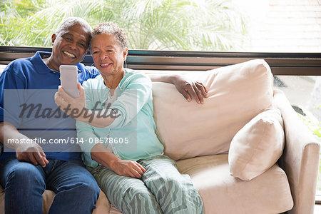 Senior couple sitting on sofa, taking self portrait using smartphone