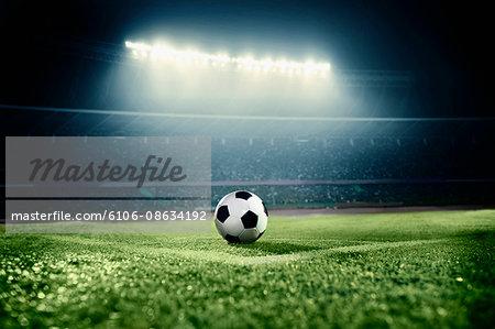Soccer ball in sports field in stadium at night