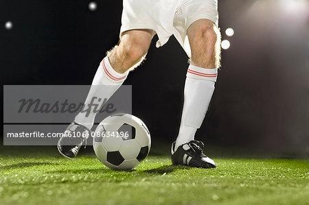 Soccer player dribbling ball across field