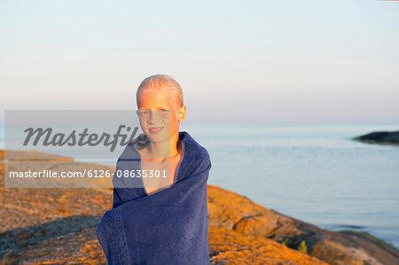 Sweden, Sodermanland, Stockholm Archipelago, Varmdo, Portrait of boy (12-13) wrapped in towel on beach