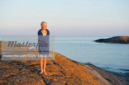 Sweden, Sodermanland, Stockholm Archipelago, Varmdo, Boy (12-13) wrapped in towel on rocky beach