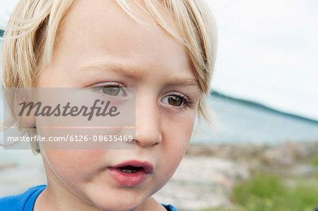 Sweden, Ostergotland, Vikbolandet, Boy (2-3) with brown eyes on beach