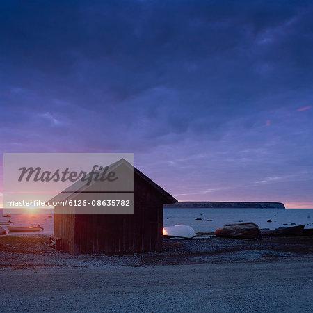 Sweden, Gotland, Eksta Coast, Wooden house on seashore at sunset