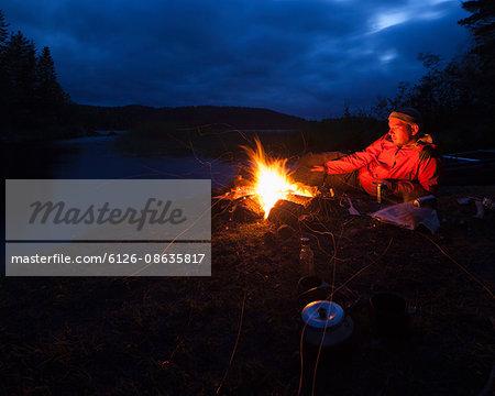 Sweden, Vastmanland, Svartalven, Man by bonfire on riverbank