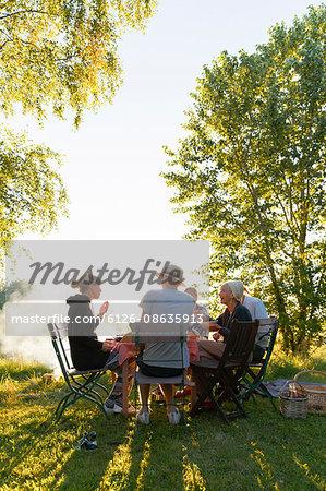 Sweden, Sodermanland, Jarna, Family having dinner in backyard at sunset