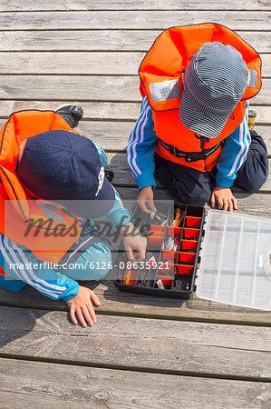 Sweden, Stockholm Archipelago, Grasko, Boys (4-5, 6-7) playing with fishing equipment