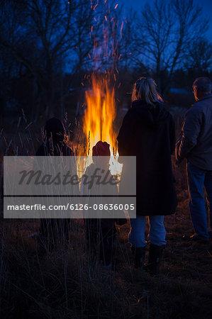 Sweden, Narke, Filipshyttan, Grandfather with grandchildren (6-7,8-9,16-17) looking at bonfire
