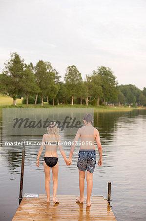 Sweden, Smaland, Braarpasjon, Girl (10-11) and boy (12-13) standing on edge of jetty