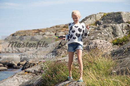 Sweden, Vastergotland, Lerum, Blonde girl (10-11) with fishing rod toy on rock