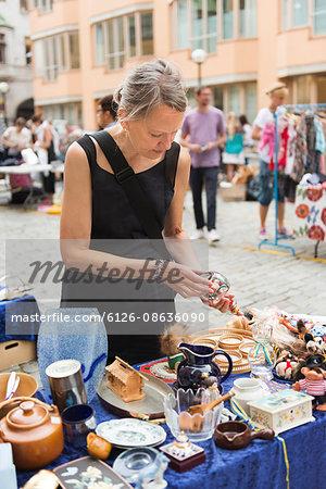 Sweden, Stockholm, Normalm, Blasieholmstorg, Portrait of mature woman choosing tableware at flea market